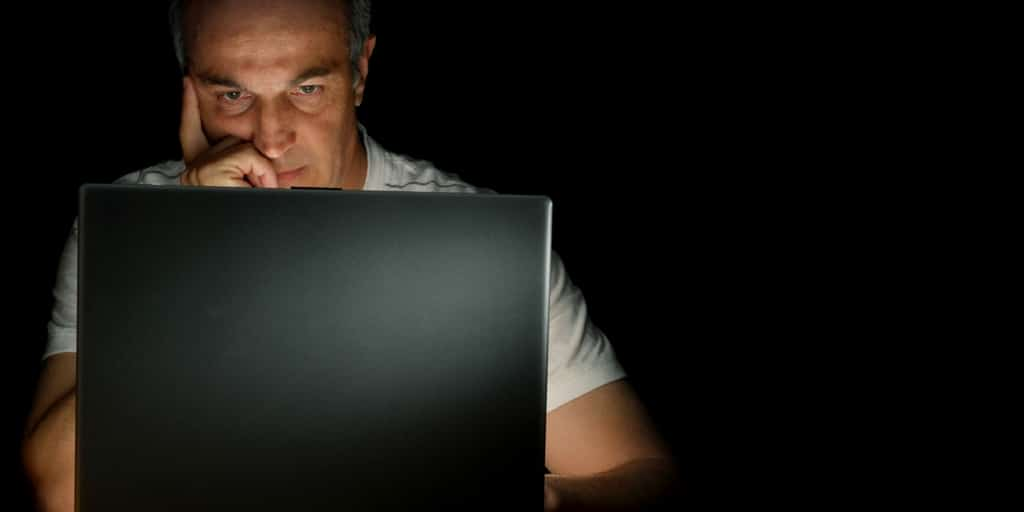 Young-man-researching-cloud-migration-strategy-on-his-laptop
