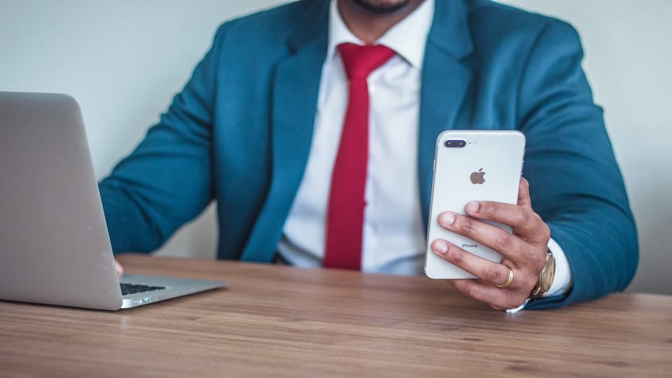 man-in-blue-suit-holding-iphone